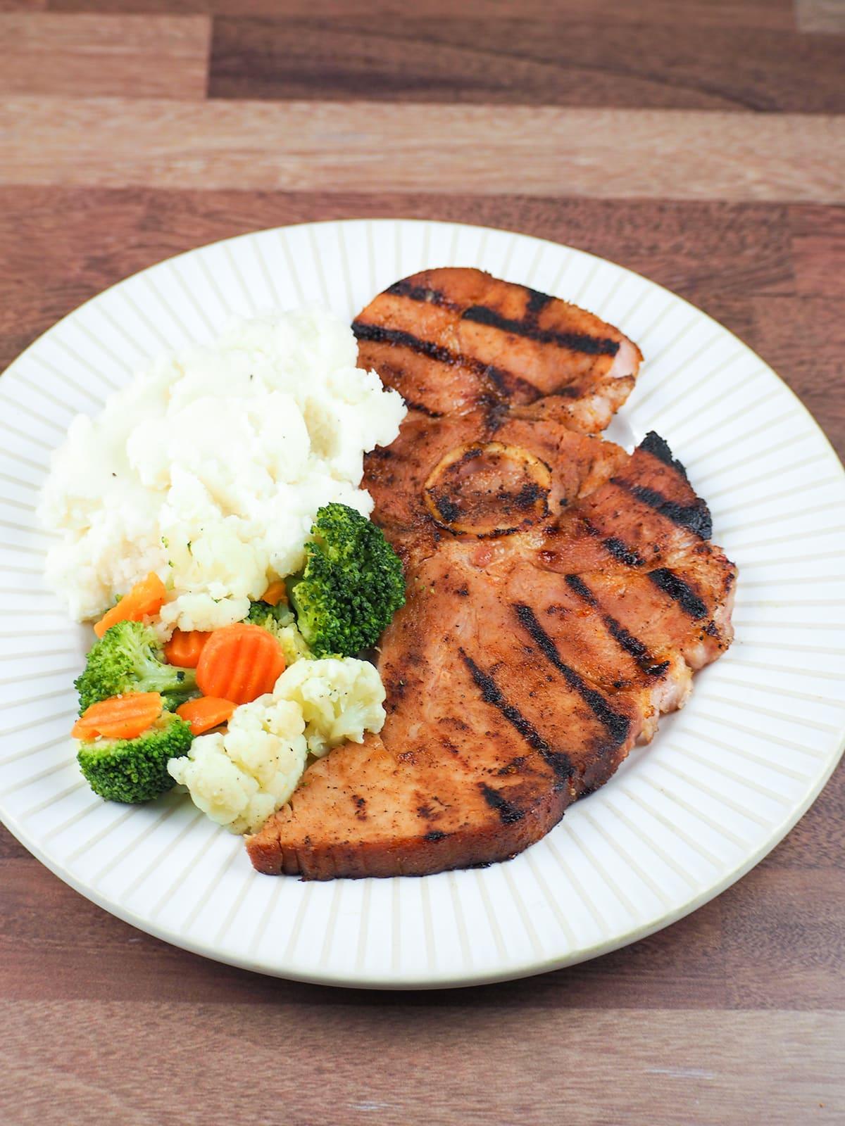ham steak dinner on white plate