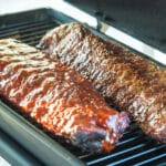 ribs with bbq sauce cooking on smoker