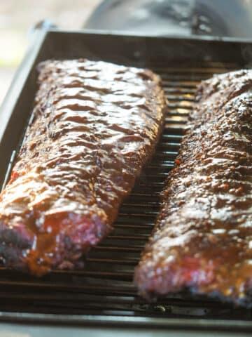 two racks of ribs inside smoker