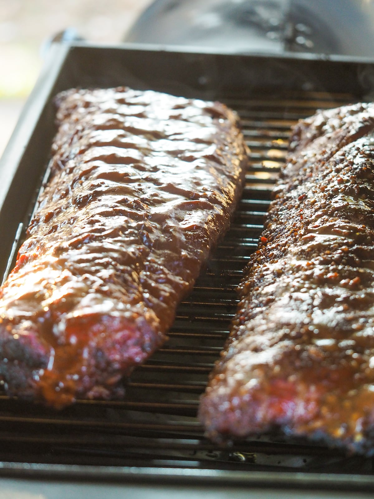 vertical picture of two racks of ribs laying on smoker
