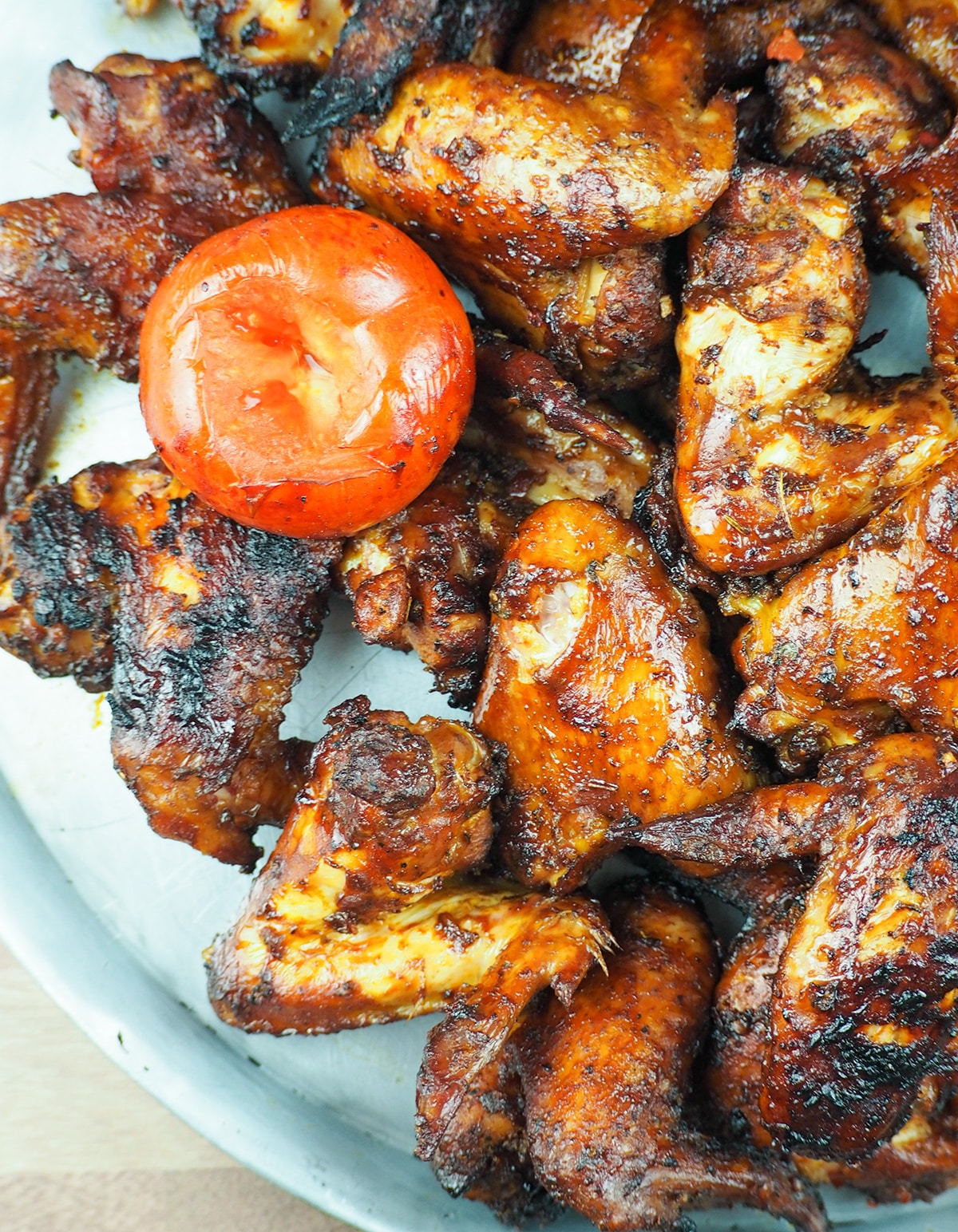 smoked chicken wings on baking sheet with smoked tomato