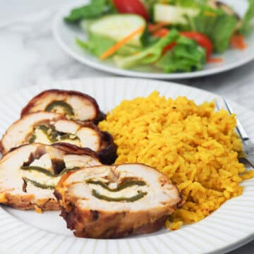 sliced jalapeno popper on white plate with yellow rice