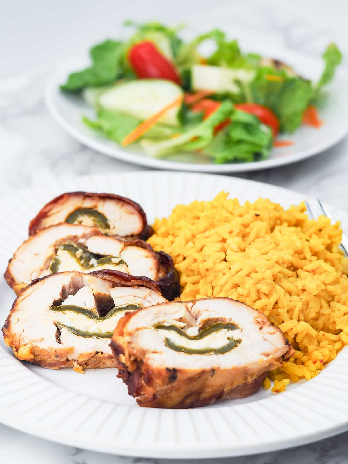 sliced jalapeno popper chicken on plate with yellow rice and vegetables with salad plate in background