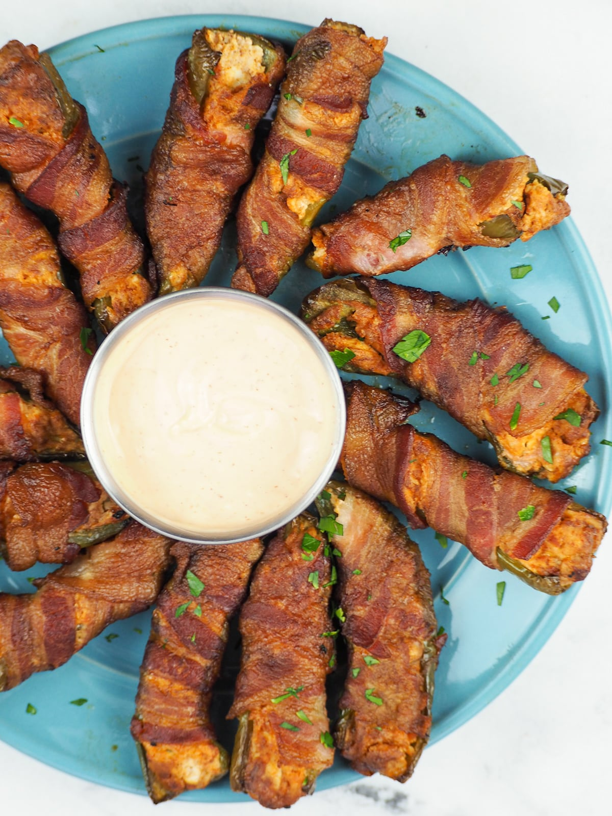 smoked jalapeno poppers arranged in a ring around a cup of dipping sauce on a blue plate