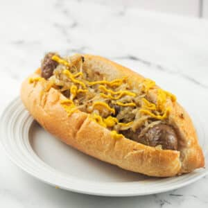 bratwurst with sauerkraut in hoagie bun topped with mustard on white plate