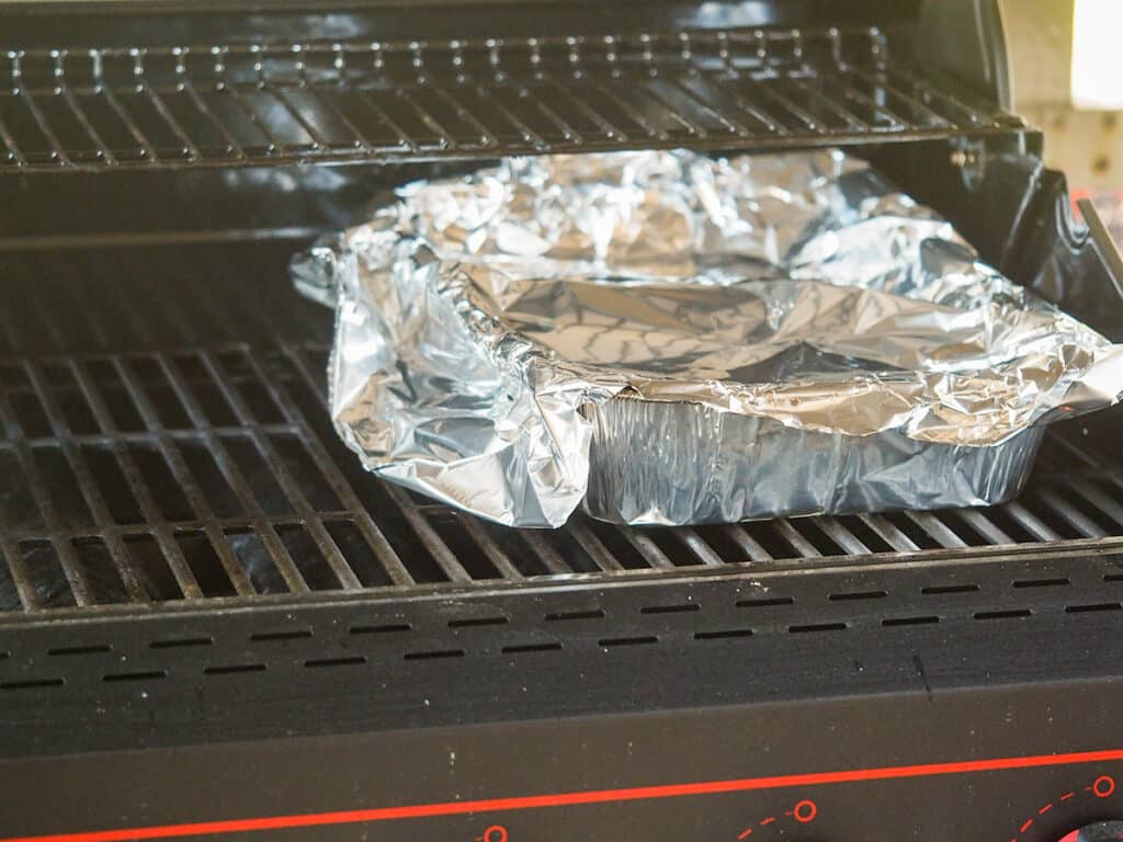 aluminum pan on grill covered with foil