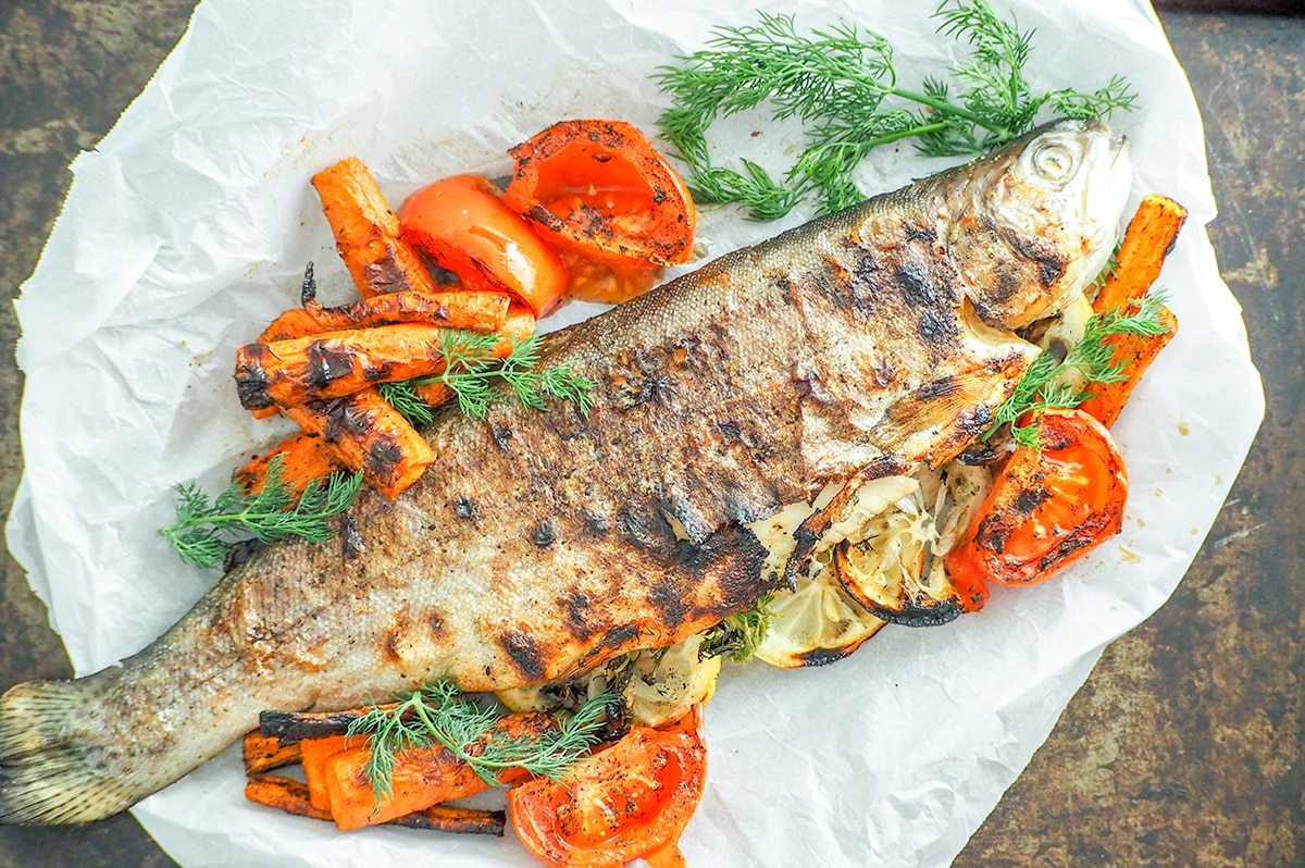 grilled trout on baking sheet sitting on parchment paper with roasted vegetables
