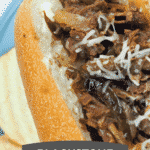 philly cheesesteak on blue plate with chips